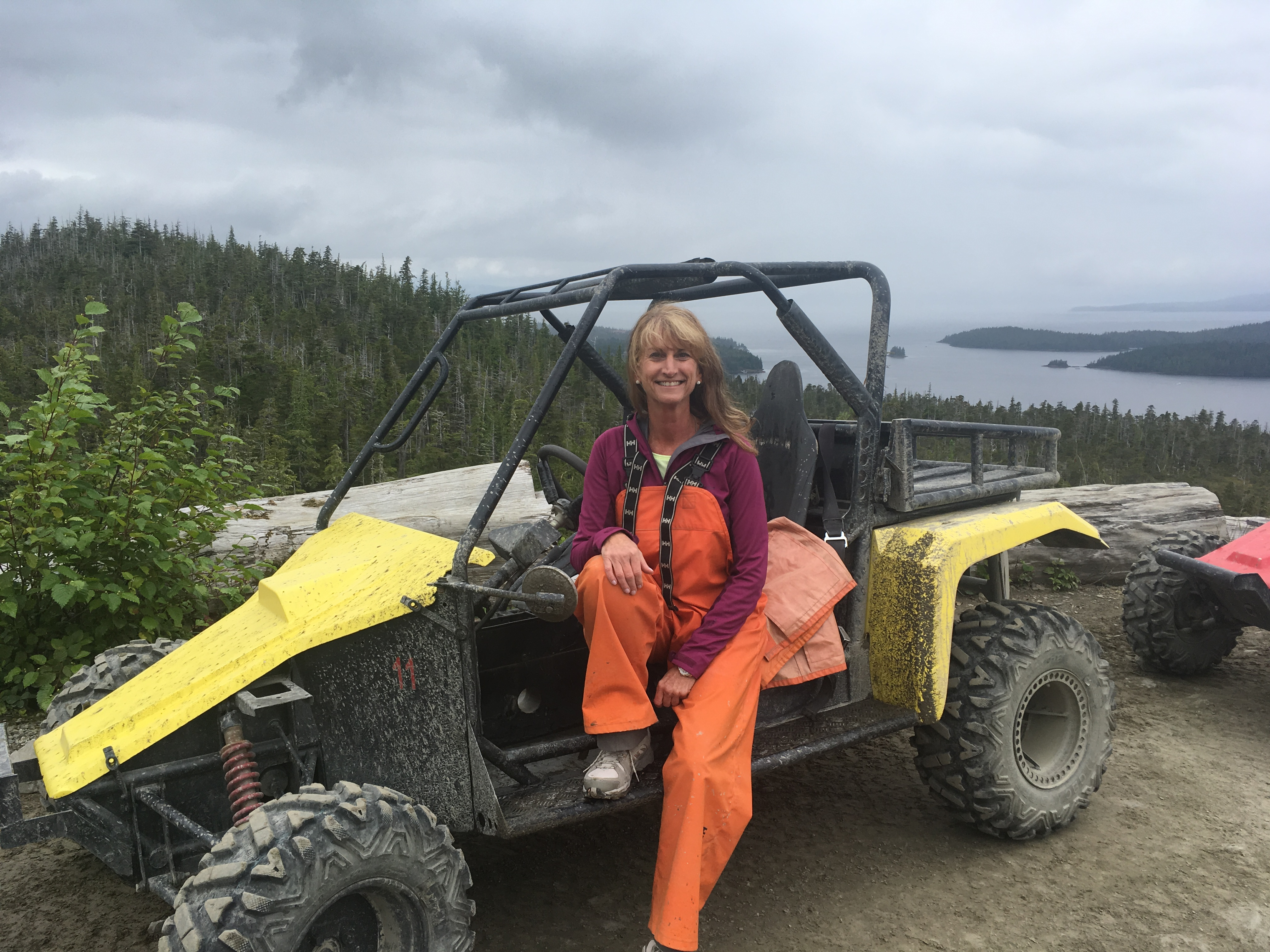 Photo of Debbie Wircenske sitting on a yellow All Terrain Vehicle (ATV) on a mountain top