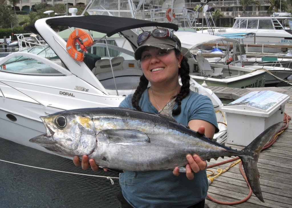 Photo of Yonah Cohen in front on a boat holding a tuna she caught